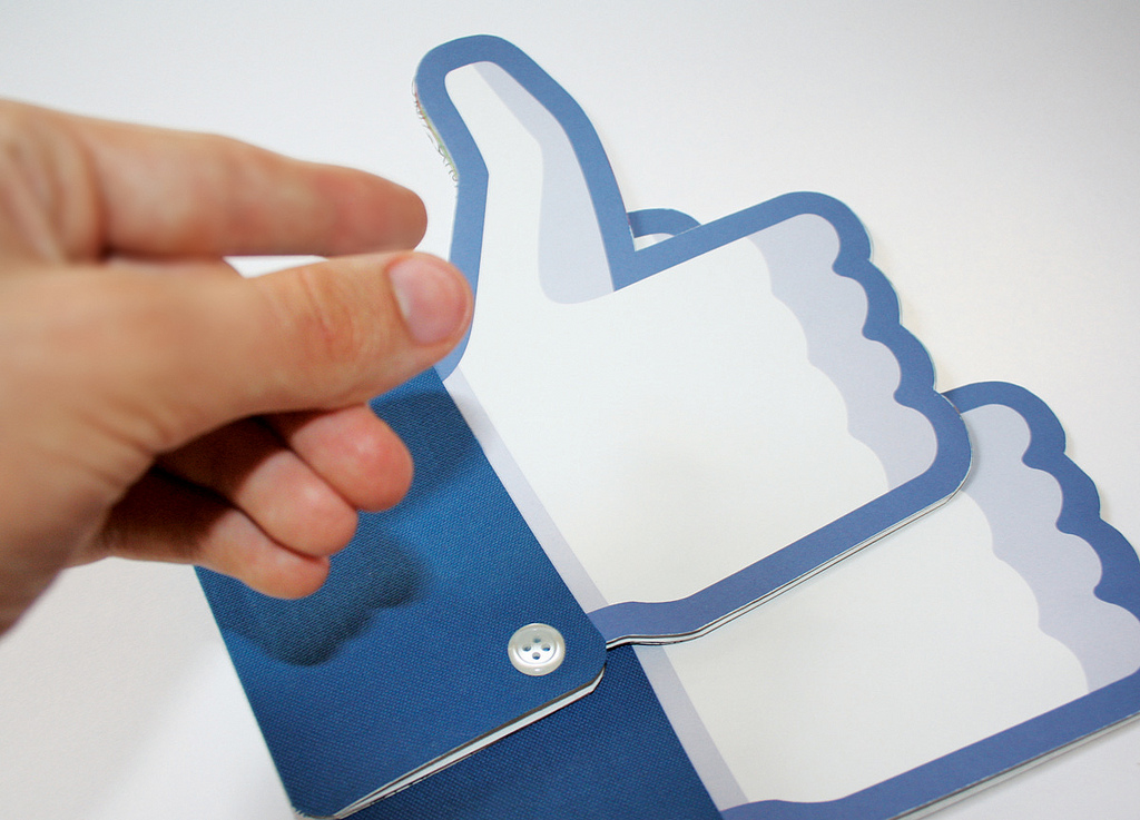 A hand picking up real life mock-ups of the Facebook Like button.