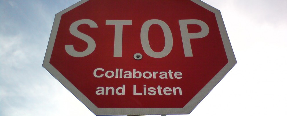 A sign with graffiti saying stop, collaborate and listen.